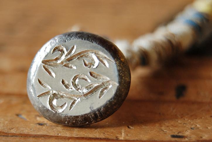 小さなチャームに繊細なアラベスクの彫りもよう。